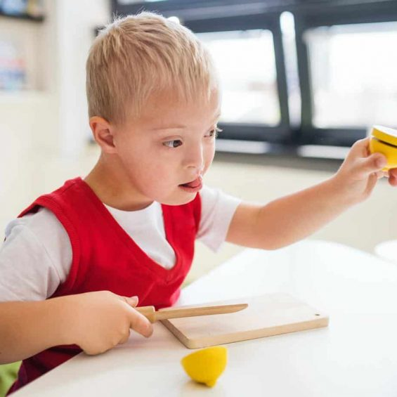 A down-syndrome school boy sitting at the desk in the classroom, learning