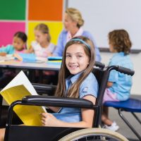 Disabled school girl on wheelchair holding a book in classroom