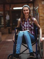 Disabled schoolgirl on wheelchair in corridor at school